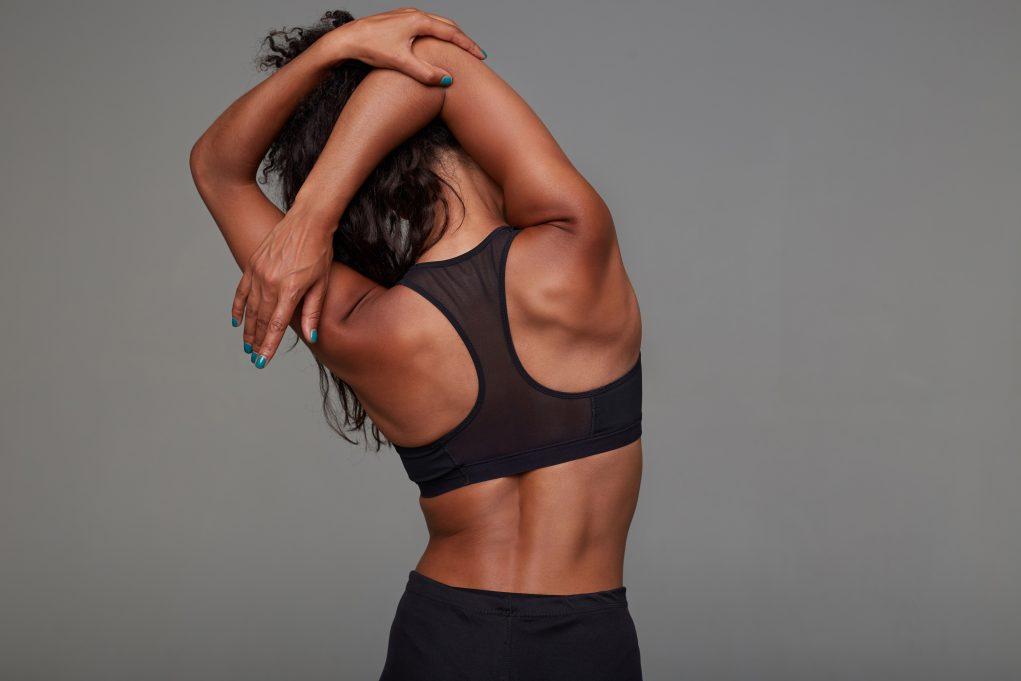 back view young athletic dark skinned curly brunette female stretching her hands while posing black sporty top fitness female model