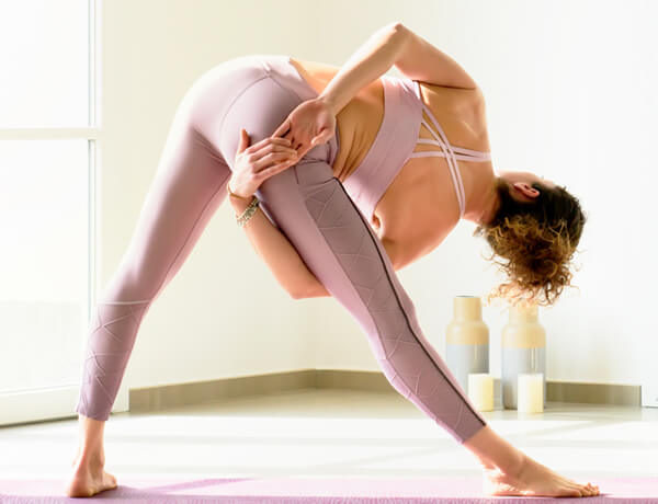 woman doing triangle yoga pose indoors R2GN9DV
