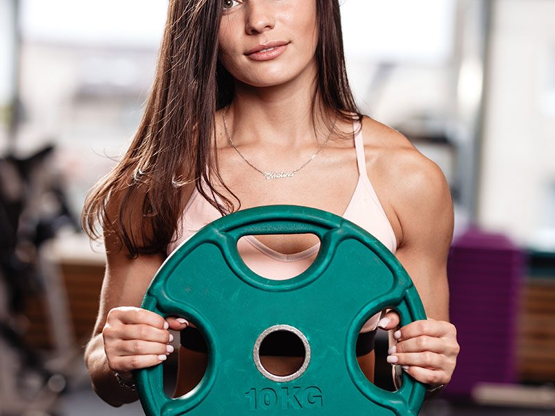 athletic-young-brunette-girl-holds-a-heavy-plate-F4QQH2Q.jpg